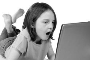 Little girl looks shocked at something she sees on the computer