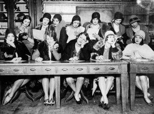 Women in 1920's apparel at a long wooden desk, writing letters
