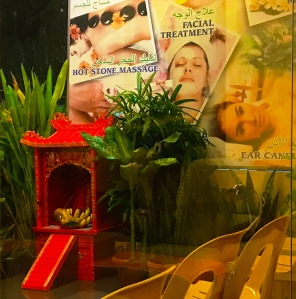 A small red shrine in front of a wall covered in massage advertisements