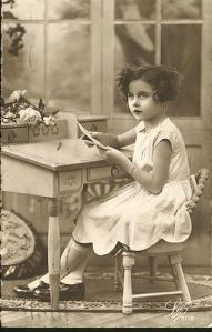 Vintage sepia photo of young girl with dark curly hair sitting at desk holding a paper and looking thoughtful