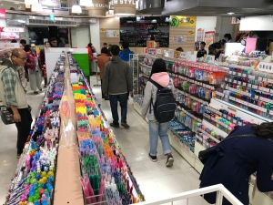 Photo of stationery store, three aisles of pens.