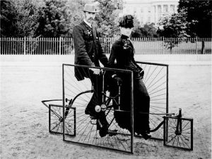 Vintage black and white photo of man and woman in Victorian dress on penny farthing bicycle with square wheels.