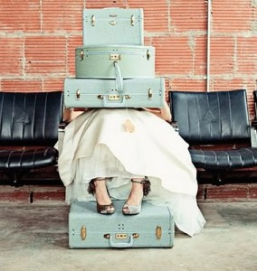 vintage photo of light blue suitcases stacked on lap, woman's heeled shoes and puffy white skirt showing, feet are resting on another suitcase
