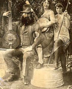 vintage daguerrotype of a man with a mandolin, a woman with a banjo, and another woman with a washtub bass. They are dressed in 1920's clothing.