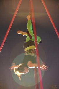 Photo of an aerial silks performer in black leotard and green tights, upside down with arms out