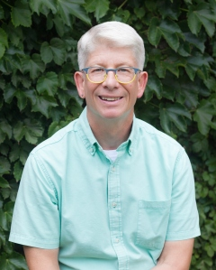 Headshot of a white man with short white hair, wire-frame glasses and a light turquoise shirt, against a background of leaves