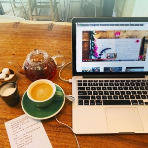 Flatlay of laptop, teacup, teapot, sugar, milk and paper on wooden table