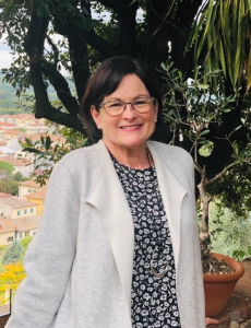A white brunette with short hair, wearing a white cape sweater and black and white patterned dress, standing on a balcony overlooking a Tuscan valley