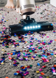 A vacuum on a beige carpet, picking up shiny confetti