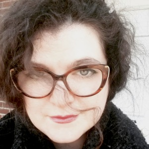 author headshot of a white woman with dark curly hair and tortoiseshell glasses. A lock of hair is across her face.