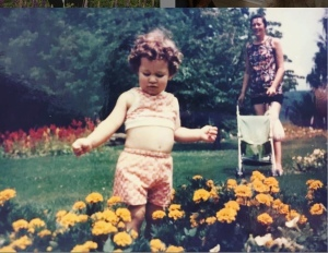A white toddler, her belly hanging out of her top and shorts, among chrysanthemums. Behind her, her mother holds a walker.