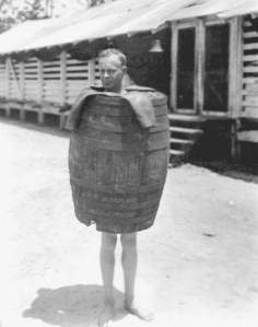 Black and white vintage photo of man wearing a bankruptcy barrel