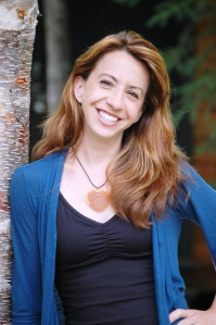 author headshot of strawberry blonde white woman with black tank, blue cardigan and statement necklace