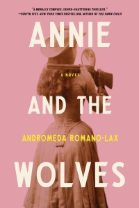 Cover image of Annie and the Wolves, a pink book with a sepia photo of Annie Oakley aiming a gun with a mirror over her shoulder